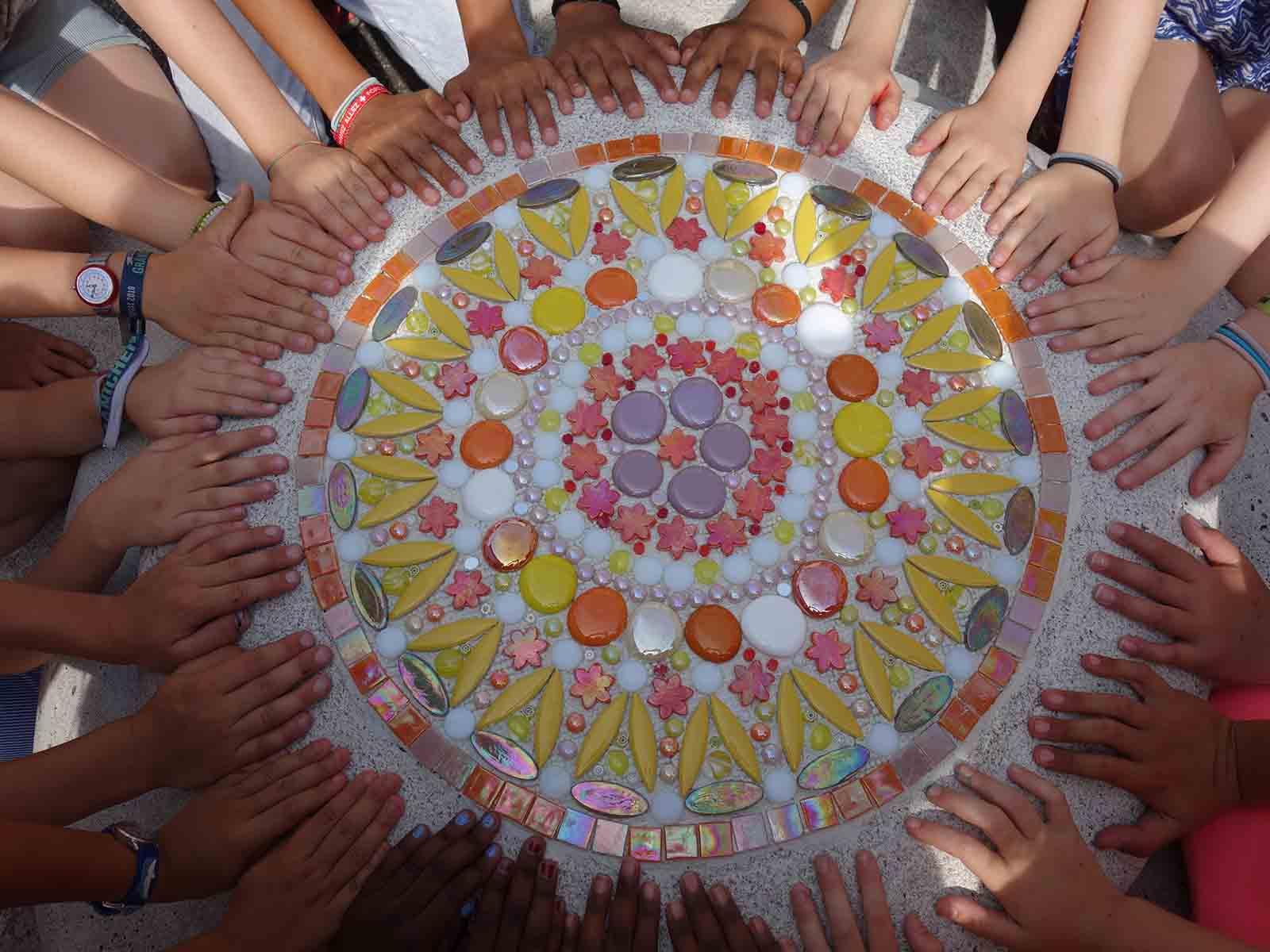 Künstlerhände um das fertige Mosaik.