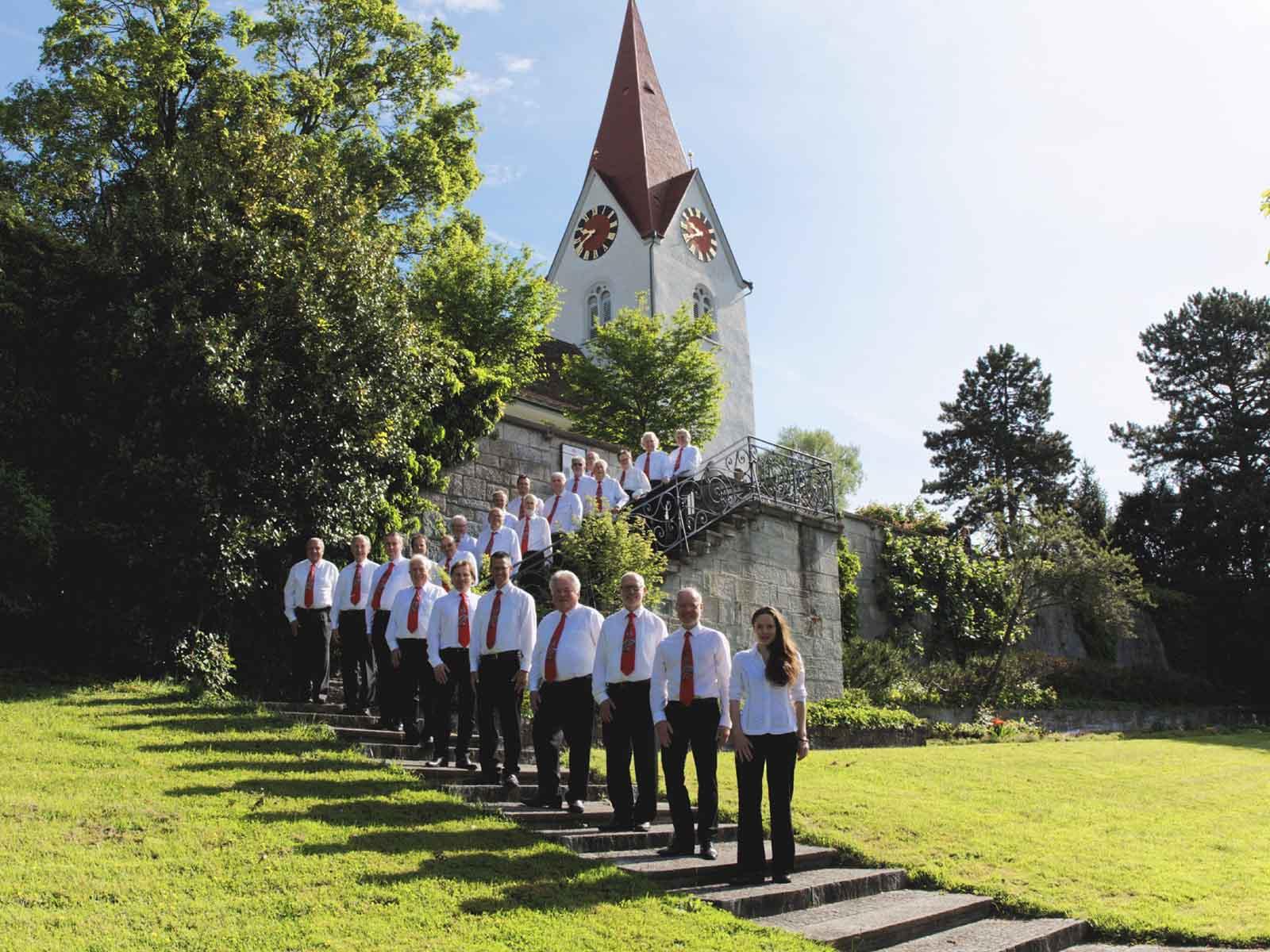 Der stolze Männerchor mit Dirigentin vor der Reformierten Kirche Höngg.