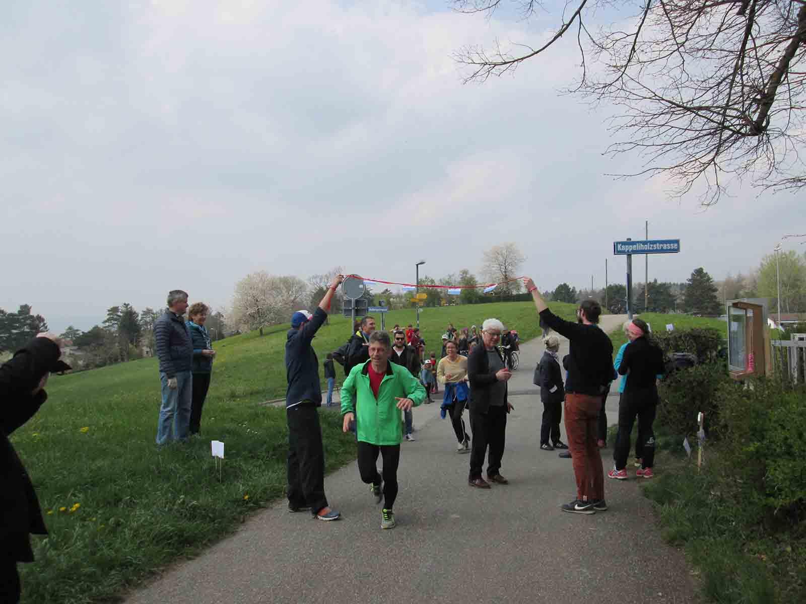 Roby Zwicky, Präsident des Turnvereins Höngg hält die Schere zum Durchschneiden des Bandes noch in der Hand, als die ersten Läufer*innen bereits starten.