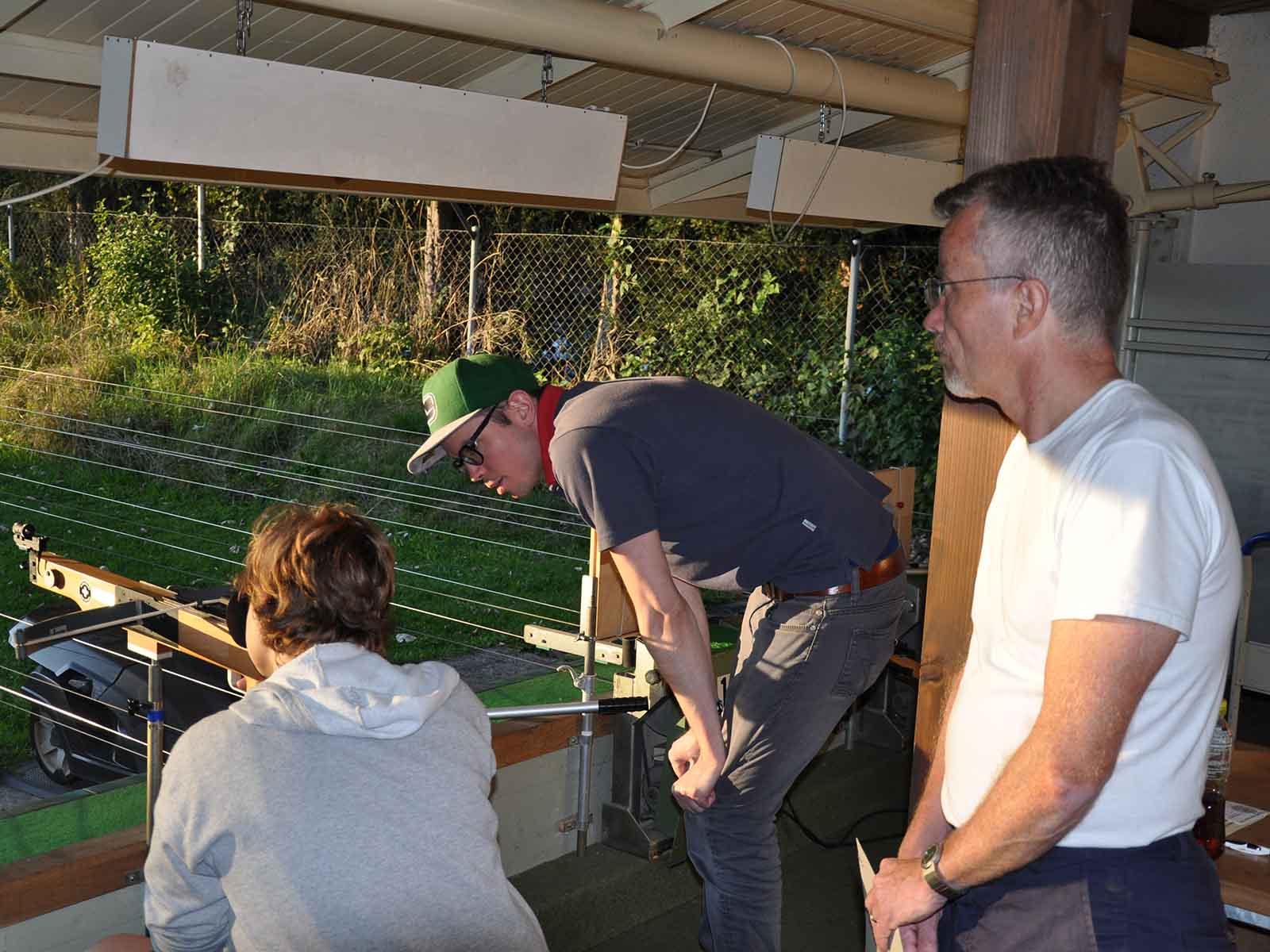 Der Vize-Weltmeister Marco Vetsch instruiert einen neugierigen Jungen, der mit seinem Vater (rechts) gekommen ist.
