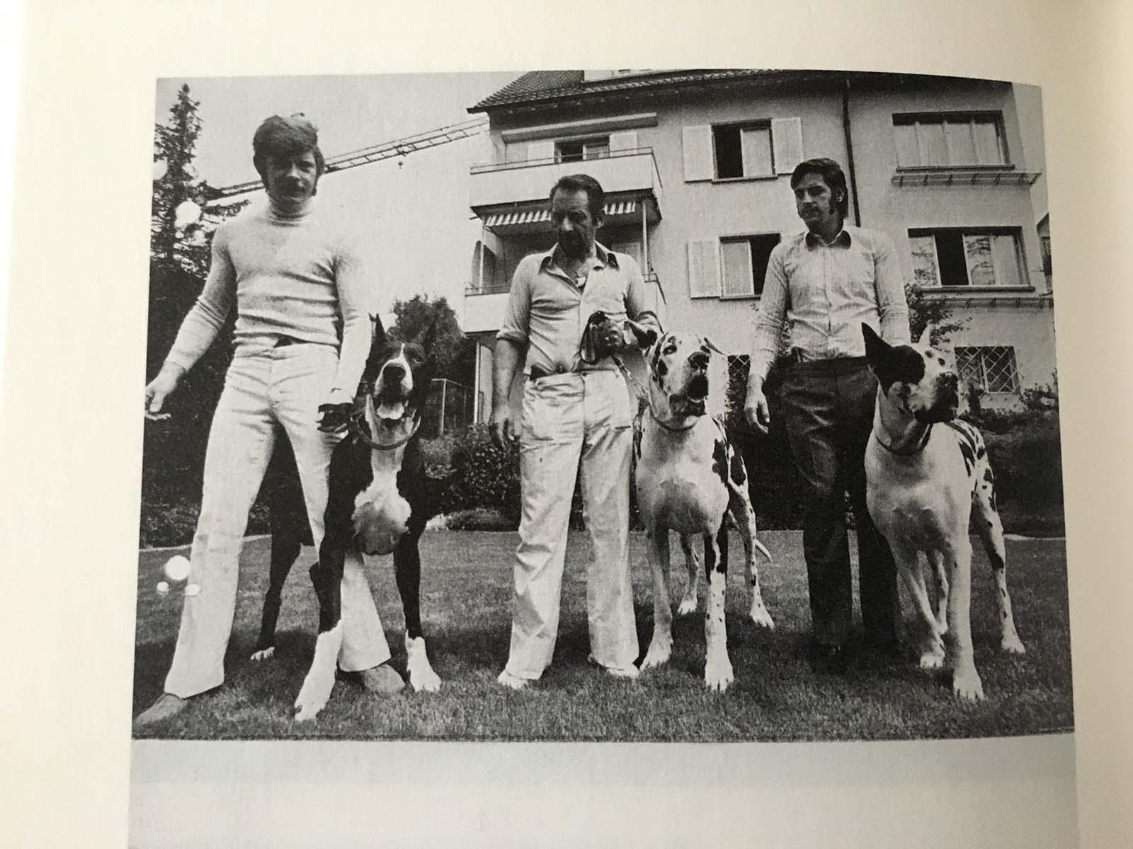 Lenzlinger und zwei Mitarbeiter präsentieren sich mit Doggen und Waffen vor dem Haus an der Ackersteinstrasse.