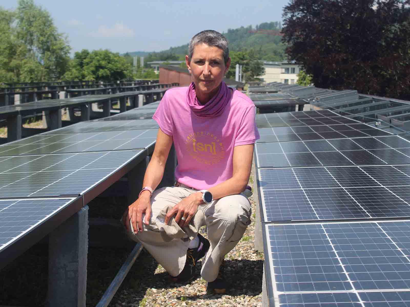 Im Rütihof wird Strom produziert: Iris Hassenpflug, Projektleiterin beim «ewz», inmitten der Solarmodule auf dem Schulhausdach.
